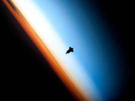 shuttle Endeavor silhouetted against Earth as seen from the ISS...
