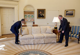 President Obama and Vermont Governer Jim Douglas move a couch in the oval office, aka rearranging deck chairs on the Titanic