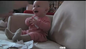 baby laughing at paper being torn